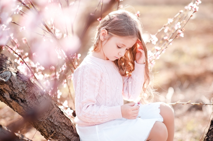 Cute baby girl sitting on tree playing with flowers outdoors. Childhood.