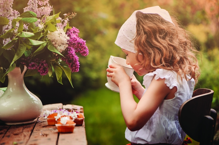 cute child girl on cozy outdoor tea party in spring garden with